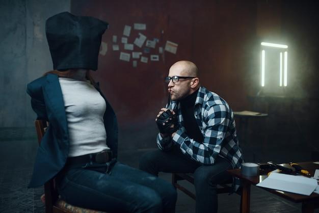 Маньяк-похититель смотрит на свою жертву с сумкой на голове. похищение - серьезное преступление, сумасшедший мужской психопат, ужас похищения, насилие Premium Фотографии