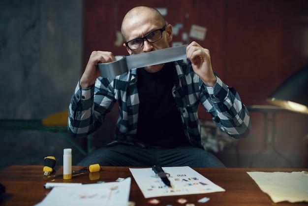 Маньяк-похититель готовит клейкую ленту для своей жертвы. похищение - серьезное преступление, мужской психопат, ужас похищения, насилие Premium Фотографии