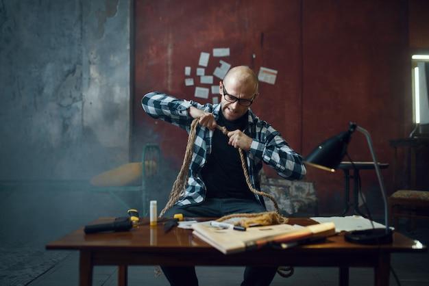 Маньяк-похититель готовит веревку для своей жертвы. похищение - серьезное преступление, мужской психопат, ужас похищения Premium Фотографии