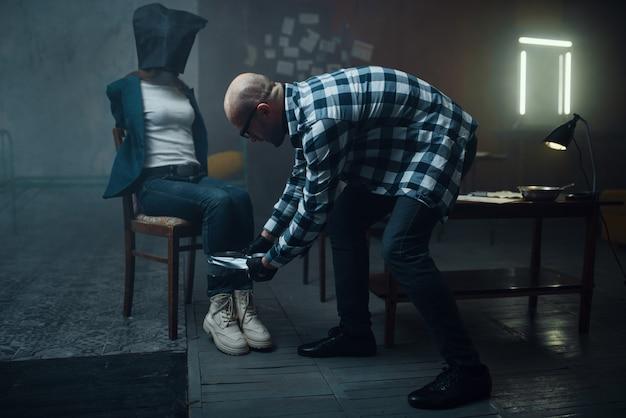 Маньяк-похититель заклеивает ноги своей жертвы. похищение - серьезное преступление, сумасшедший мужской психопат, ужас похищения, насилие Premium Фотографии