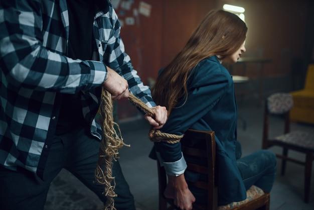 Маньяк-похититель связывает свою жертву веревкой. похищение - серьезное преступление, сумасшедший мужской психопат, ужас похищения, насилие Premium Фотографии