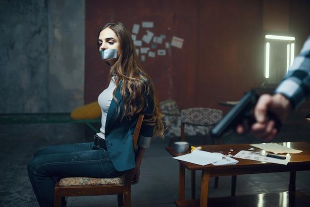 Похититель маньяка с ружьем, испуганная жертва на фоне. похищение - серьезное преступление, сумасшедший мужской психопат, ужас похищения, насилие Premium Фотографии