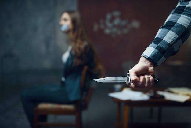 Похититель маньяка с ножом, испуганная жертва на фоне. похищение - серьезное преступление, сумасшедший мужской психопат, ужас похищения, насилие Premium Фотографии
