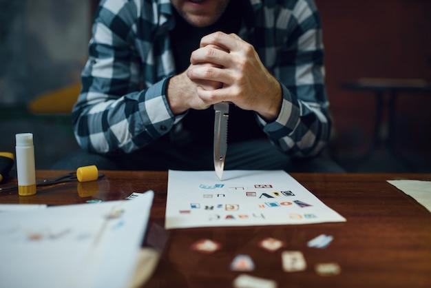 Похититель маньяка с ножом смотрит на текст, состоящий из вырезанных букв. похищение - серьезное преступление, мужской психопат, ужас похищения, насилие Premium Фотографии