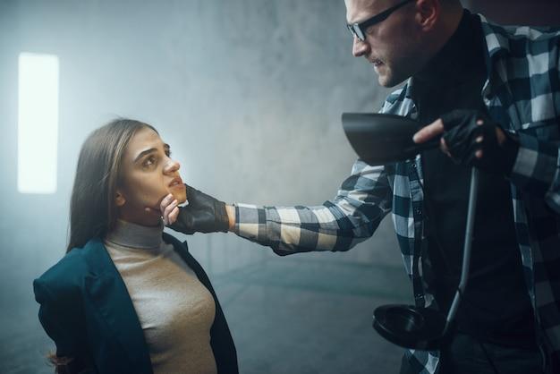 Маньяк светит фонариком в лицо своей жертве Premium Фотографии