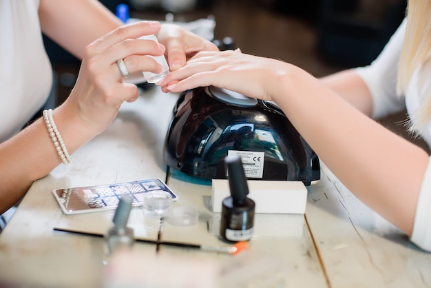 Manicure procedure with pattern and silver nails polish Premium Photo