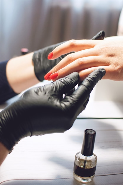 Manicure specialist in black gloves cares about nails Premium Photo