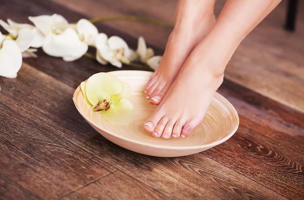 花と水のクローズアップスパ木製ボウルに手入れの行き届いた女性の足 Premium写真