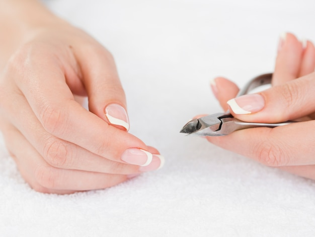 Manicured hands holding nail clipper Free Photo