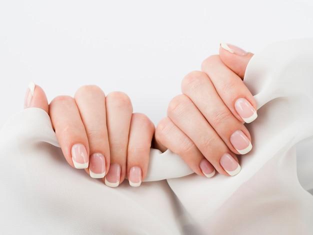 Ухоженные руки держат мягкую ткань Premium Фотографии