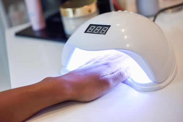 Manicured nails in uv lamp in beauty salon. Free Photo