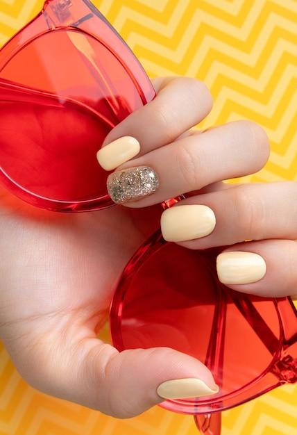 最小限のスタイルでトレンディな黄色のマニキュアで手入れの行き届いた女性の手。 Premium写真