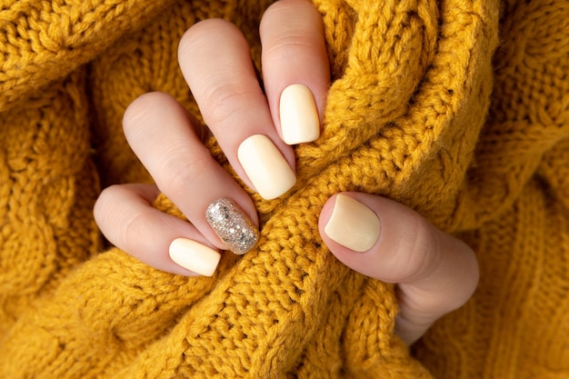 暖かいウールの黄色いセーターで手入れの行き届いた女性の手。 Premium写真