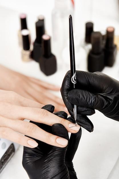 Manicure che fa arte sul dito medio, disegnando con la spazzola di arte. Foto Gratuite