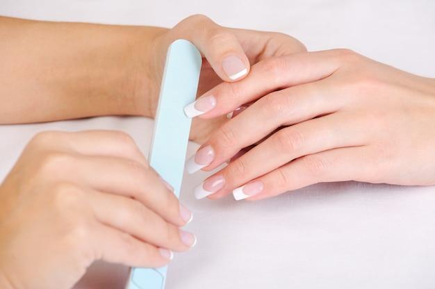 프랑스 매니큐어로 여성 손톱을 연마하는 매니큐어 사 무료 사진