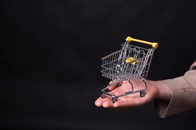 Ман рука держит небольшую тележку на черном фоне. Premium Фотографии