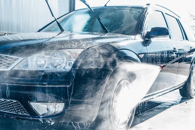 Ручная мойка автомобилей, мойка водой под высоким давлением на автомойке, концепция очистки Premium Фотографии