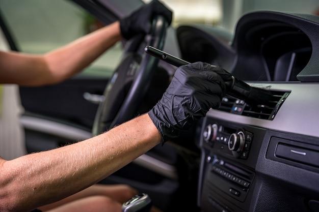 ブラッシングを使用した車内の手動クリーニング。 Premium写真