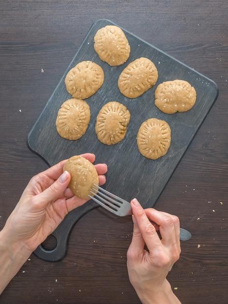 休日のためのクッキーの手動生産。エジプトクッキー「kahk el eid」の準備-el fitr islamic feastのクッキー。ラマダンのお菓子 Premium写真