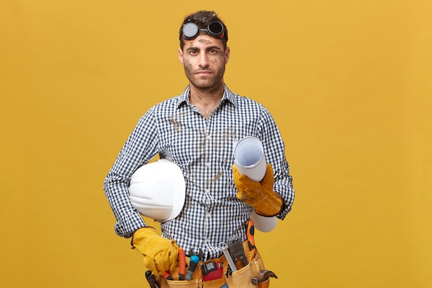 Manual work, maintenance, occupation concept. dirty mechanic man wearing goggles on head, protective gloves, shirt holding rolled paper and hardhat. hard-working young builder with instruments Free Photo