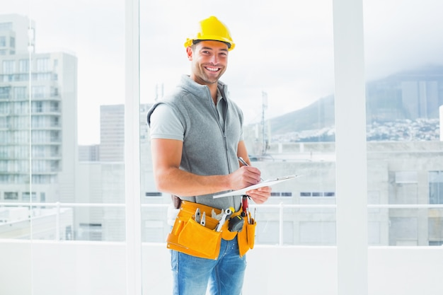 Manual worker writing on clipboard in building Premium Photo
