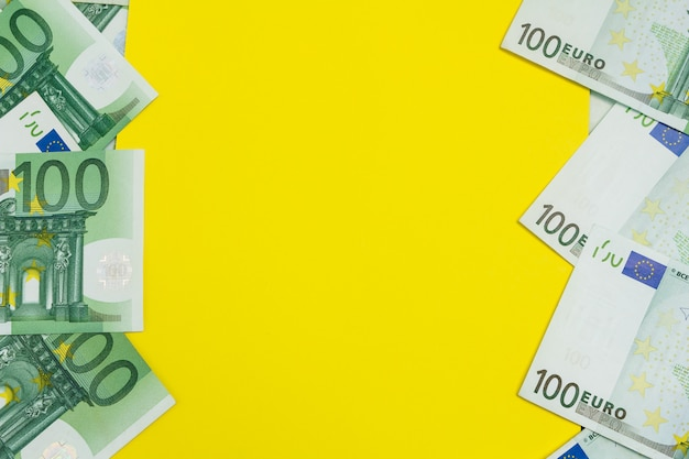 Many banknotes of 100 euro with yellow copy space, the european currency background flat lay Premium Photo