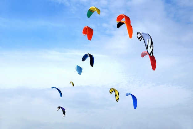 Many big colorful sport kites flying high in bright blue sky on sunny day Premium Photo