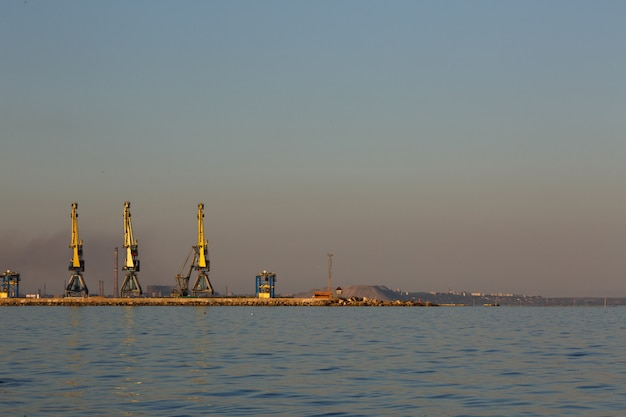 Many big cranes silhouette in the port at golden light of sunset. mariupol, ukraine Premium Photo