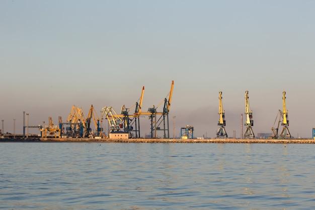 Many big cranes silhouette in the port at golden light of sunset. mariupol, ukraine Premium Photo