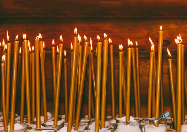 Many burning wax candles in the temple Premium Photo