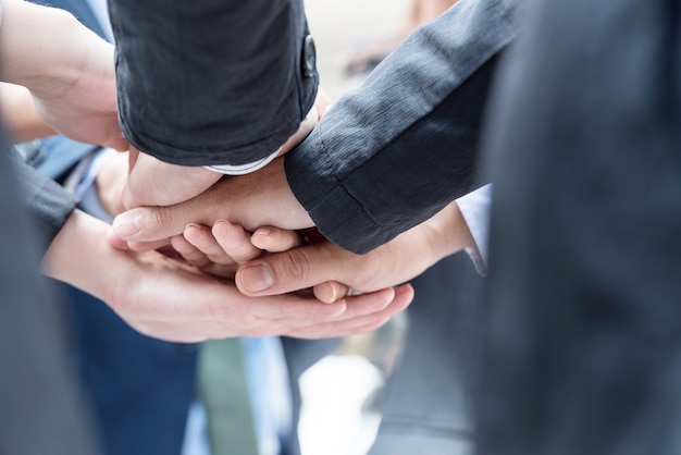 Many business people join hands together for the first agreement to do business together Premium Photo