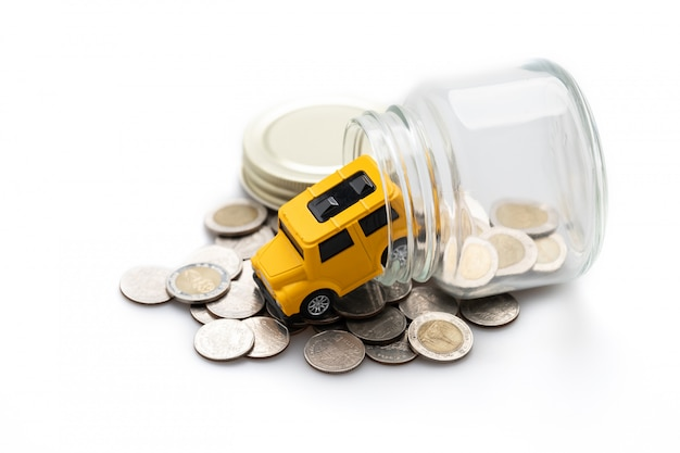 Many coins in a glass jar and a yellow toy car Premium Photo