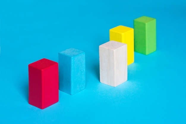 Many colored blocks in a row and one wooden block on blue background Premium Photo