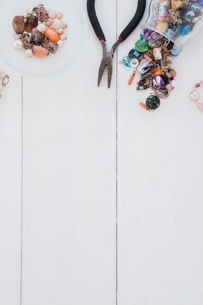 Many colorful beads and plier on wooden desk Free Photo