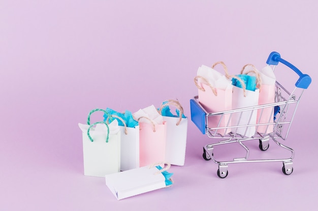 Many colorful paper shopping bags in cart on pink background Free Photo