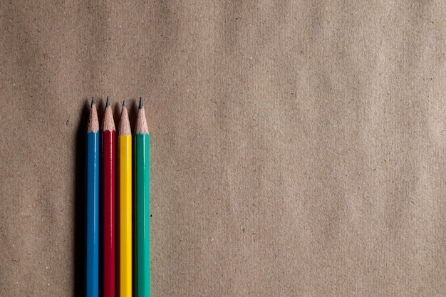 Many colorful pencils on brown paper can be applied to designs. Premium Photo