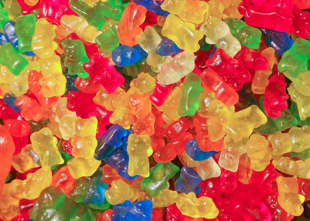 Many colorful tasty gummy bears candies. sweets background. Premium Photo