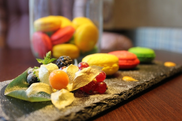 흰 접시에 크림과 함께 많은 색깔의 마카롱 프리미엄 사진