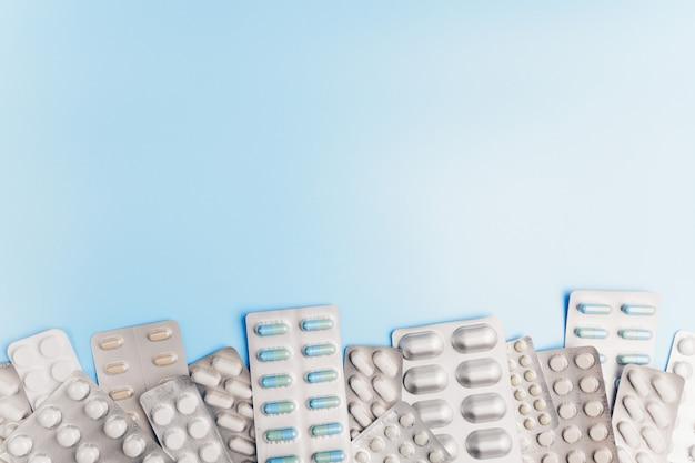 Много различных пакетов таблеток на светло-синем фоне. Premium Фотографии