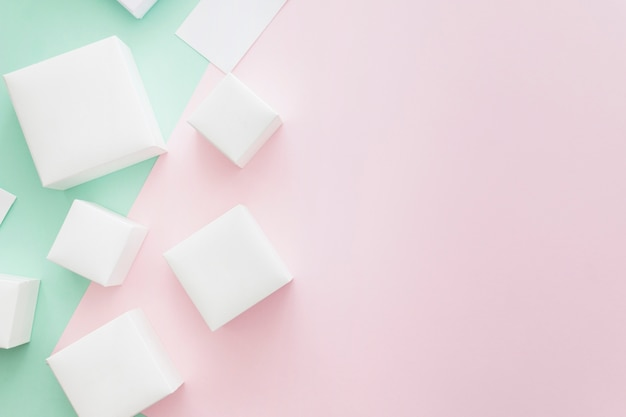 Many different white boxes on green and pink backdrop Free Photo