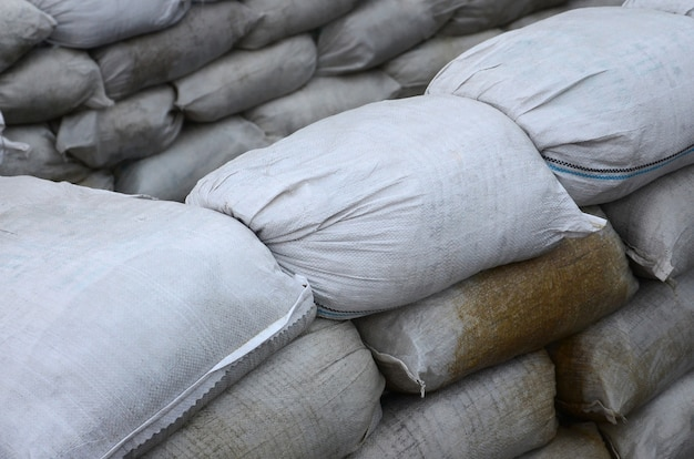 Many dirty sand bags for flood defense. protective sandbag barricade for military use. handsome tactical bunker Premium Photo