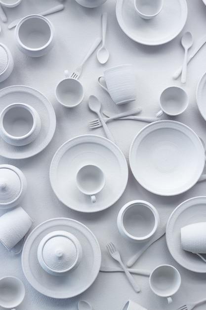 多くの皿や器具は白い表面に白く塗られています Premium写真