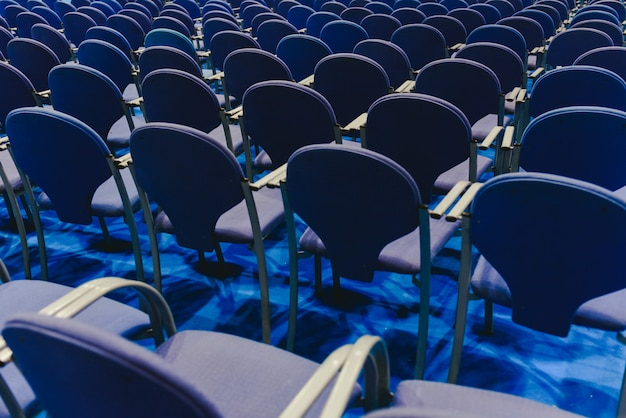 Many empty blue row chairs in a theater. Premium Photo