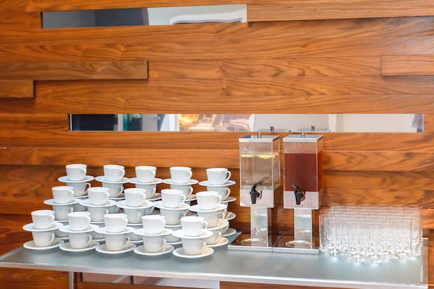 Many empty white tea or coffee cups, glasses and  big juice bottles  on the table. event catering service. Premium Photo