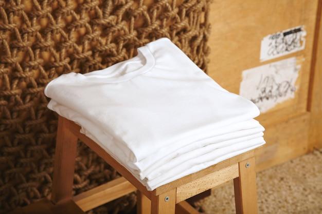 素朴なインテリアで提示された多くの折り畳まれた白い基本的な綿のtシャツ 無料写真