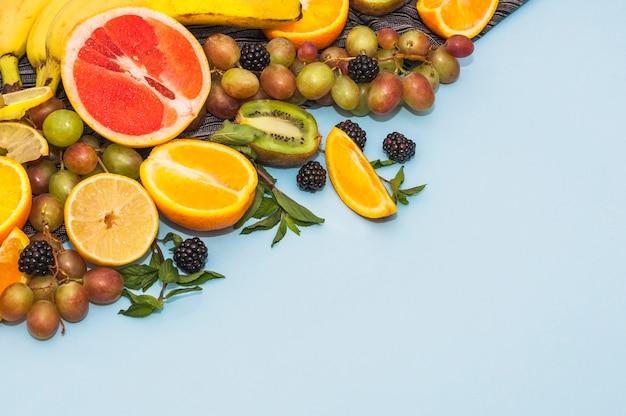 Many fresh organic fruits on blue background Free Photo