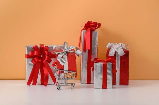 Many gift box with red ribbon bow and shopping cart or trolley on white table and pastel orange wall Premium Photo