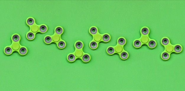 Many green fidget spinners lies on texture background Premium Photo