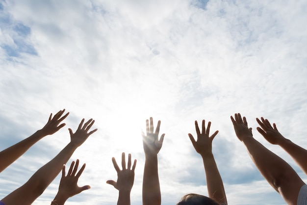 Many hands raised up against the blue sky. friendship, teamwork concept Premium Photo