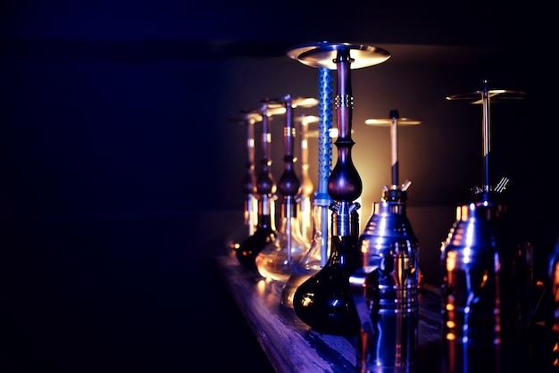 Many hookahs with shisha glass flasks and metal bowls Premium Photo